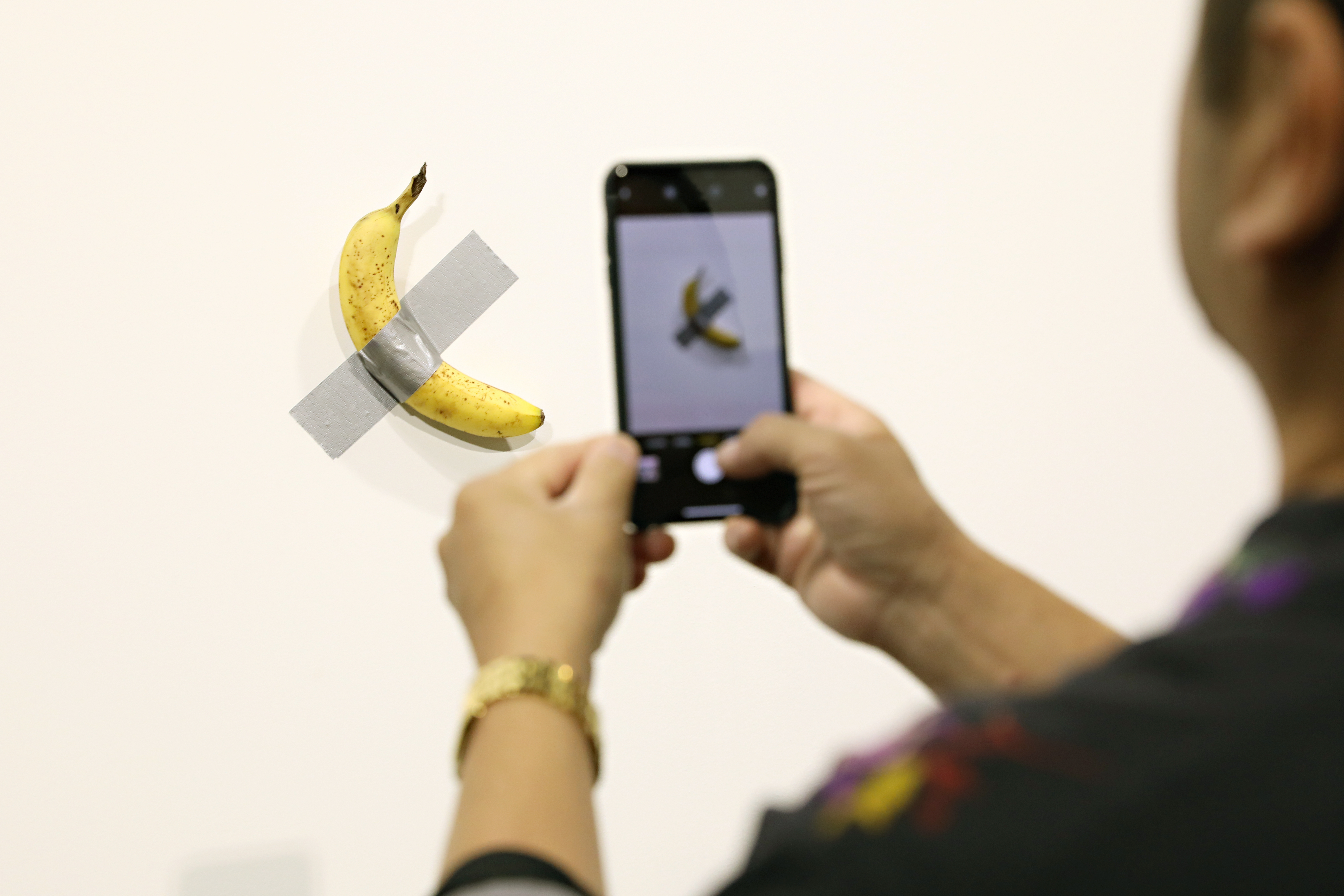 A performance artist ate a banana after it had sold for a total of $120,000 after being on display at the Galerie Perrotin during Art Basel.