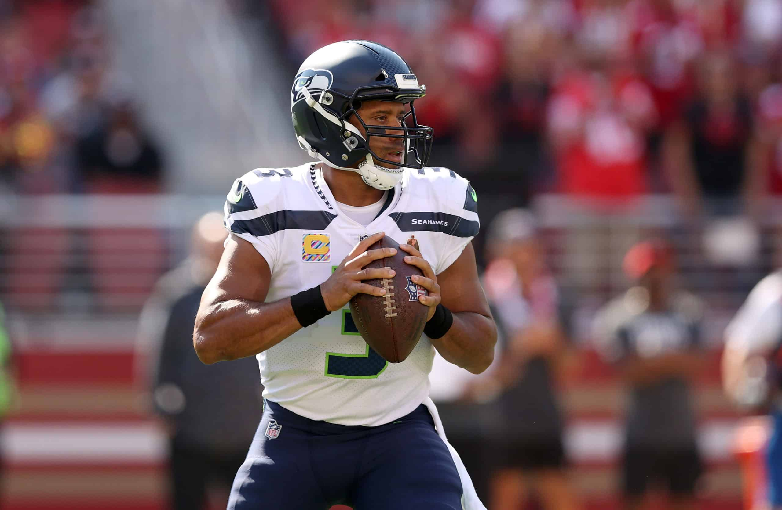 Russell Wilson celebrates becoming the fastest quarterback in the NFL to win 100 games after the Seahawks defeated the 49ers on Sunday.